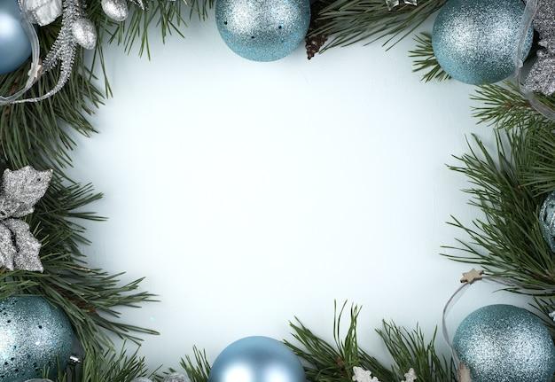 Piękna świąteczna ramka z niebiesko-srebrnymi zabawkami na niebieskiej powierzchni