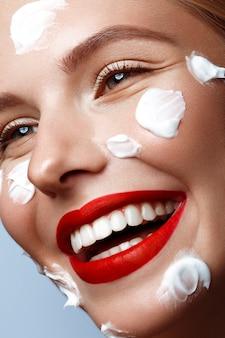 Piękna świeża dziewczyna z kremem kosmetycznym na twarz, naturalnym makijażem i czerwonymi ustami, piękna twarz,