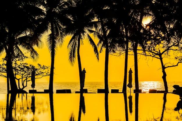 Piękna sylwetka palmy kokosowej na niebie wokół basenu w hotelowym kurorcie blisko oceanu morskiego