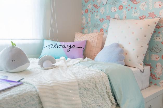 Piękna sypialnia dla dzieci ze słodkimi poduszkami i lalkami.