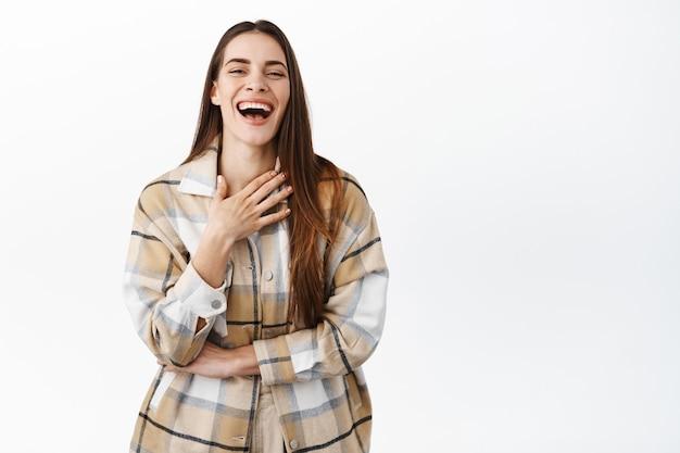 Piękna, szczera kobieta śmiejąca się naturalnie, słysząca zabawny żart, dotykająca klatki piersiowej podczas chichotu i zabawy, oglądająca komedię, stojąca przy białej ścianie
