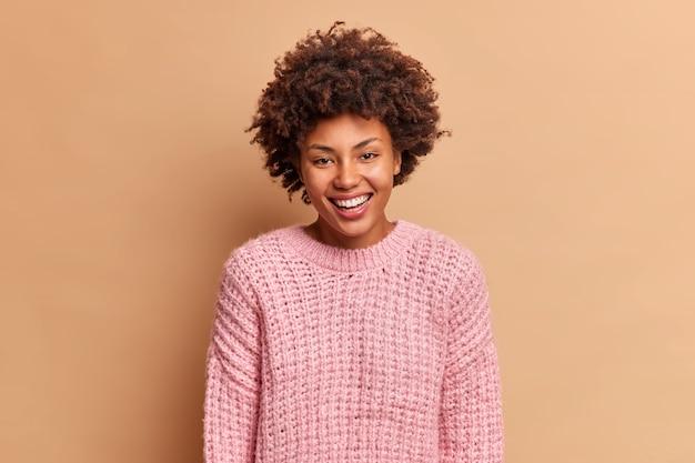 Piękna szczera kobieta z włosami afro uśmiecha się szeroko ma białe idealne zęby nie ukrywa pozytywnych emocji nosi sweter z dzianiny odizolowany na brązowej ścianie