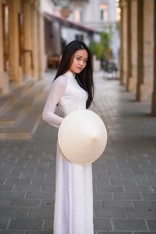 Piękna szczęśliwa azjatykcia kobieta ubierająca w ao dai sukni z wietnamskim stożkowatym kapeluszem