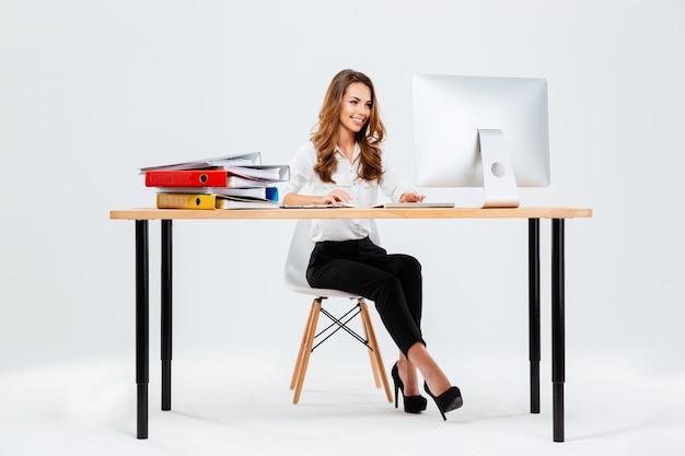 Piękna szczęśliwa bizneswoman korzystająca z komputera siedząc przy biurku w biurze isoltaed na białym tle