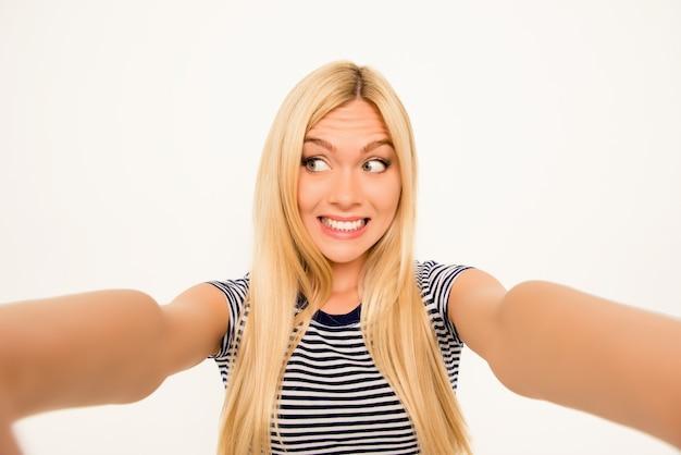 Piękna szczęśliwa blondynka robi komiczne selfie i grymasy