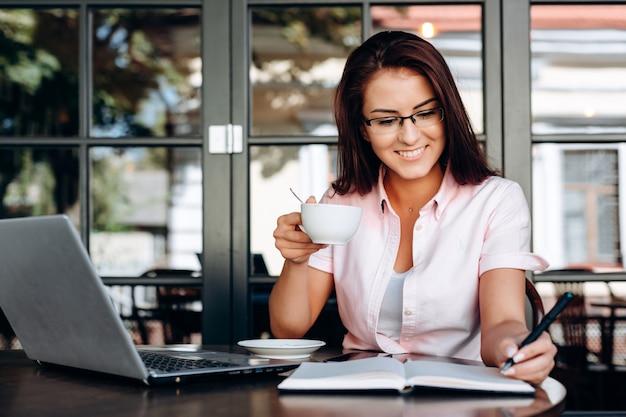 Piękna, szczęśliwa brunetka trzyma kubek w dłoni, pracuje na laptopie w kawiarni.