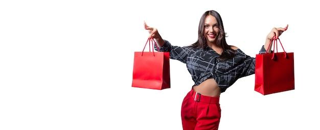 Piękna szczęśliwa brunetka z czerwonymi paczkami w dłoniach