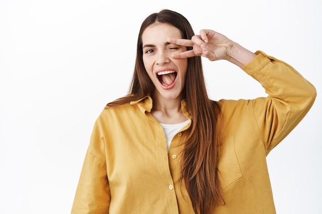 Piękna szczęśliwa dziewczyna pokazuje znak pokoju nad oczami, mrugając i uśmiechając się szeroko, wyrażając pozytywny i radosny styl życia, stojąc w stylowym stroju na białej ścianie