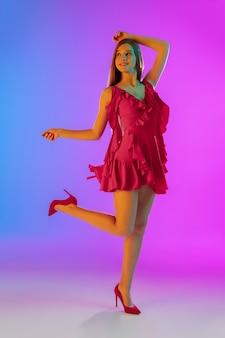 Piękna szczęśliwa dziewczyna w modnym romantycznym stroju na jasnym gradientowym fioletowym