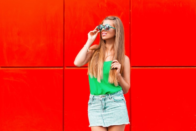 Piękna szczęśliwa dziewczyna w stylowe okrągłe zielone okulary na czerwono.