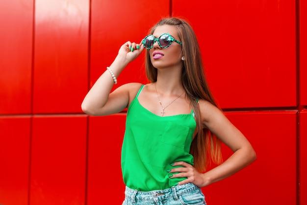 Piękna szczęśliwa dziewczyna w stylowych okularach przeciwsłonecznych w pobliżu nowoczesnej czerwonej ściany