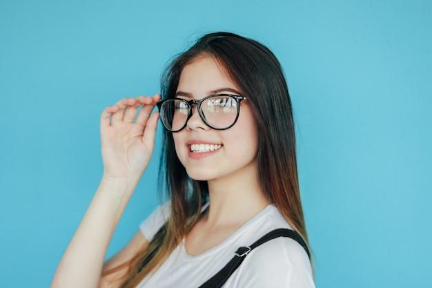 Piękna szczęśliwa dziewczyna w szkłach z ciemnym długie włosy w białej koszulce odizolowywającej na błękicie