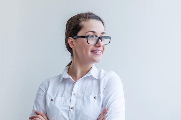 Piękna szczęśliwa dziewczyna z uśmiechem. piękno prosty portret młoda uśmiechnięta brunetka kobieta w okularach na białym tle.