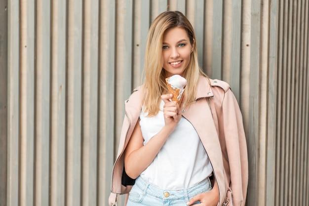 Piękna szczęśliwa dziewczyna z uśmiechem w różowej modnej kurtce je lody