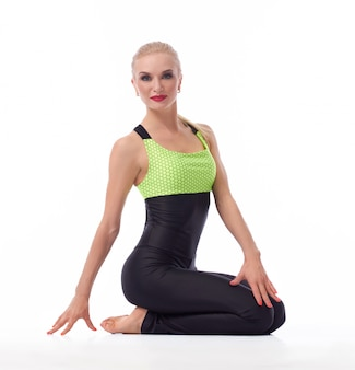 Piękna szczęśliwa fitness kobieta siedzi w pozycji lotosu uśmiechnięty na białym tle