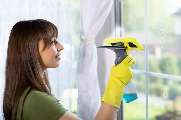 Piękna szczęśliwa gospodyni w gumowych rękawiczkach sprząta mieszkanie, wyciera szybę detergentem w sprayu, ściera kurz wycieraczką. usługa sprzątania prac domowych, prace domowe, koncepcja profesjonalnego sprzątania