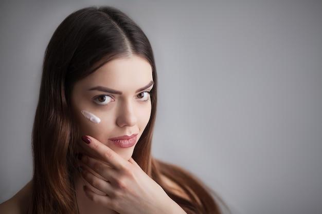 Piękna szczęśliwa kobieta nakładająca krem kosmetyczny na czystą twarz