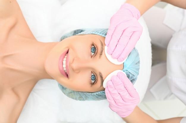 Piękna szczęśliwa kobieta otrzymywa zdroju traktowanie. kosmetolog w salonie piękności czyszczenia twarzy kobiety. piękno twarzy. dziewczyna model spa z idealnie świeżą, czystą skórą. koncepcja pielęgnacji młodzieży i skóry