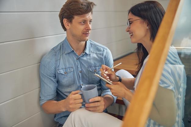 Piękna szczęśliwa kobieta pisze coś w notatniku, podczas gdy mężczyzna z filiżanką kawy w dłoni patrzący na kobietę