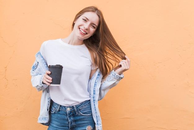 Piękna szczęśliwa kobieta pozuje blisko beżowego tła z trzymać rozporządzalną filiżankę