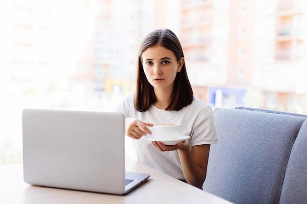 Piękna szczęśliwa kobieta pracuje na laptopie podczas kawowej przerwy w kawiarnia barze