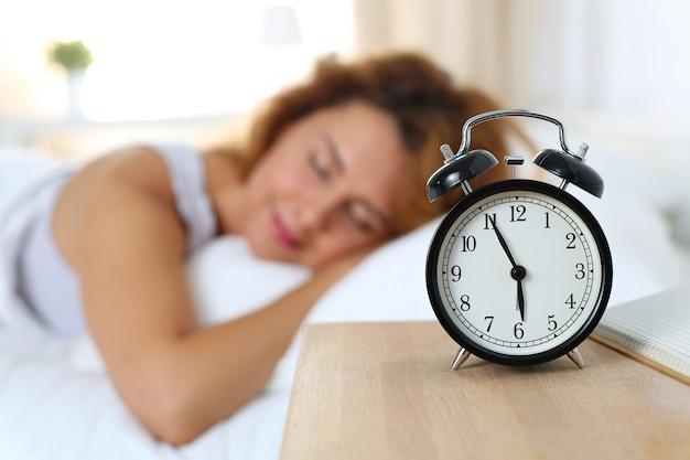 Piękna szczęśliwa kobieta śpi w swojej sypialni w godzinach porannych. dobre samopoczucie i koncepcja zdrowego snu.