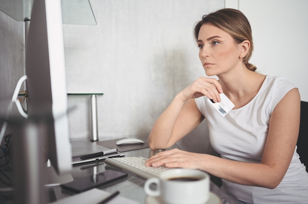 Piękna szczęśliwa kobieta trzyma kredytową kartę w ręce i używa laptop komputer klawiaturę. bizneswoman lub przedsiębiorca pracujący. zakupy online, e-commerce, bankowość internetowa, koncepcja wydawania pieniędzy