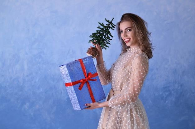 Piękna szczęśliwa kobieta trzyma małą choinkę i niebieski prezent z czerwoną wstążką w dłoniach