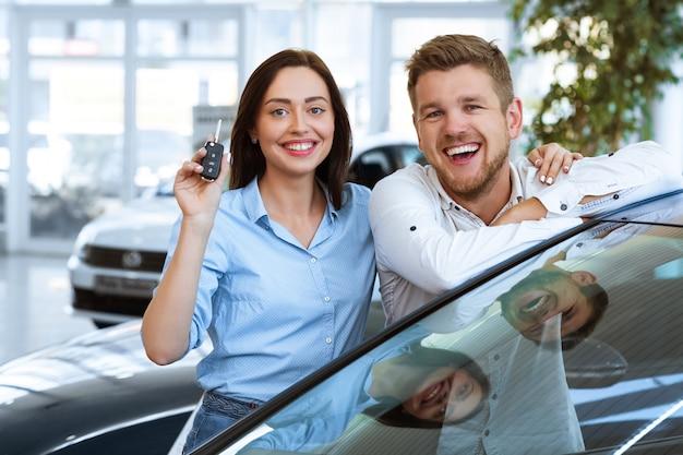 Piękna szczęśliwa kobieta uśmiecha się pokazując klucze do nowego samochodu, które właśnie kupili z mężem