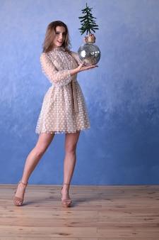 Piękna szczęśliwa kobieta w beżowej sukience trzymająca błyszczącą kulę dyskotekową i małą choinkę