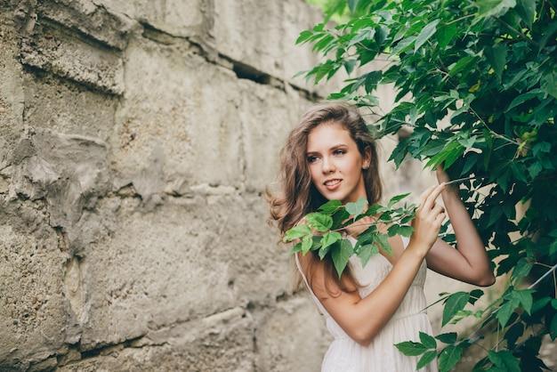 Piękna szczęśliwa kobieta w białej sukni w pobliżu zielonych liści drzew