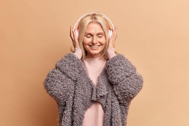 Piękna szczęśliwa kobieta w średnim wieku słucha ulubionej muzyki w słuchawkach, trzyma zamknięte oczy i uśmiecha się z satysfakcją, nosi ciepły płaszcz, spędza wolny czas słuchając przyjemnych piosenek w pozach w domu