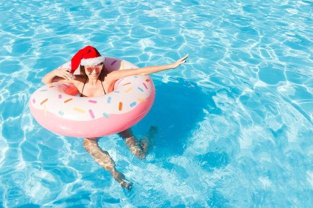Piękna szczęśliwa kobieta w świątecznym kapeluszu z nadmuchiwanym pierścieniem relaksujący w niebieskim basenie