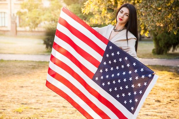 Piękna szczęśliwa kobieta z amerykańską flagą z okazji dnia niepodległości.