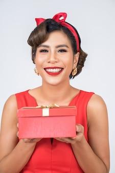 Piękna szczęśliwa kobieta z niespodzianka prezenta pudełkiem