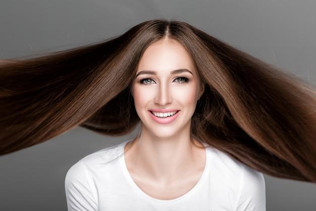 Piękna szczęśliwa kobieta z przepięknymi lśniącymi długimi włosami latającymi. pielęgnacja włosów