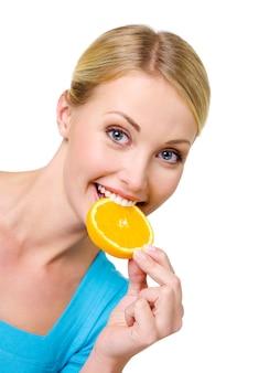 Piękna szczęśliwa kobieta zjada kawałek świeżego plastra pomarańczy - na białym tle