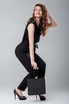 Piękna szczęśliwa kręcona kobieta w czarnym eleganckim kombinezonie z torbą na zakupy