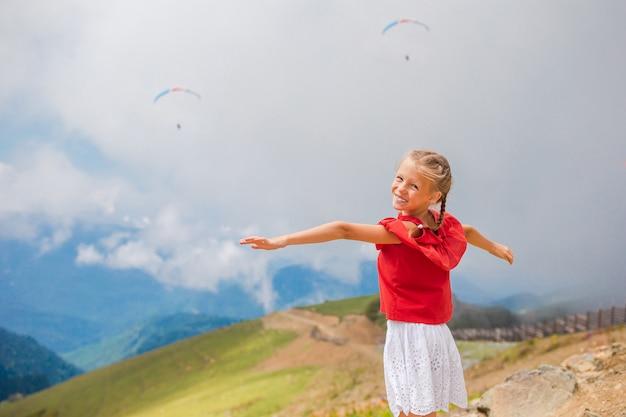 Piękna szczęśliwa mała dziewczynka w górach w tle mgła
