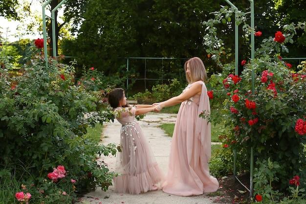 Piękna szczęśliwa matka i córka, trzymając się za ręce i uśmiechając się w pięknych identycznych długich sukienkach