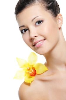 Piękna szczęśliwa młoda azjatykcia dziewczyna z żółtą orchideą na ramieniu