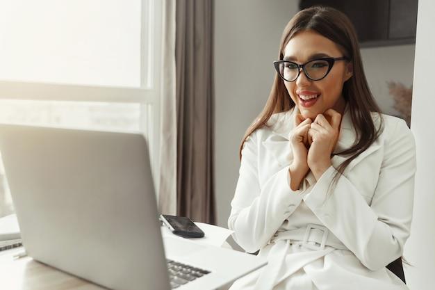 Piękna szczęśliwa młoda bizneswoman, kobieta za pomocą laptopa i uśmiechnięta podczas pracy w pomieszczeniu. biuro domowe podczas kwarantanny koronawirusa lub covid-19. komunikuje się w internecie.