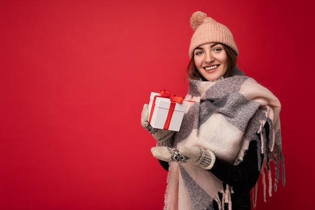 Piękna szczęśliwa młoda brunetka kobieta na białym tle nad kolorową ścianą na sobie stylowe ubranie, trzymając pudełko i patrząc na kamery