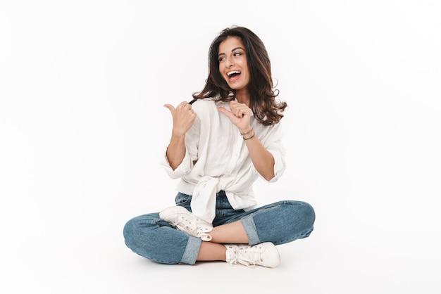 Piękna szczęśliwa młoda brunetka kobieta ubrana w zwykłe ubranie, siedząca na podłodze ze skrzyżowanymi nogami na białym tle nad białą ścianą, wskazując palcami daleko