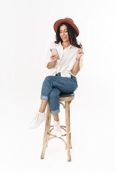 Piękna szczęśliwa młoda brunetka w stroju casual, siedząca na wysokim krześle na białym tle nad białą ścianą, przy użyciu telefonu komórkowego