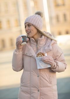 Piękna szczęśliwa młoda dorosła kobieta pije kawę jest ubranym zimę odziewa i ono uśmiecha się. piękna kobieta trzyma papierową filiżankę na zewnątrz w mieście.