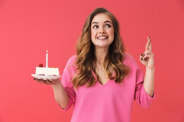 Piękna szczęśliwa młoda dziewczyna ubrana w zwykłe ubrania, stojąca na białym tle nad różową ścianą, świętująca urodziny z ciastem