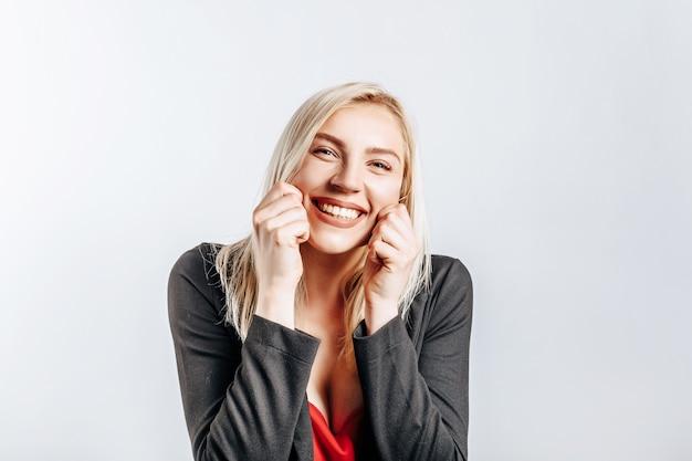 Piękna szczęśliwa młoda dziewczyna uśmiecha się na szarym odosobnionym tle