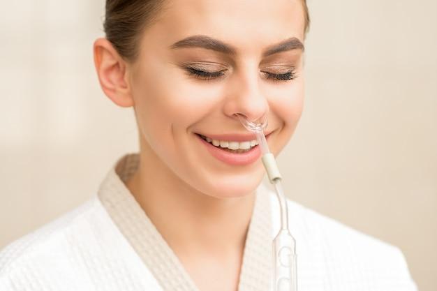 Piękna szczęśliwa młoda kobieta kaukaska otrzymująca inhalator do nosa z olejkiem eterycznym uśmiechnięta w spa