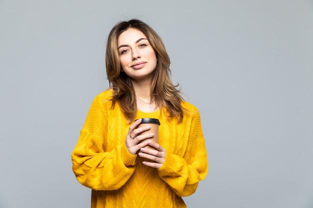 Piękna szczęśliwa młoda kobieta odizolowywająca nad szarości ścianą pije kawę.